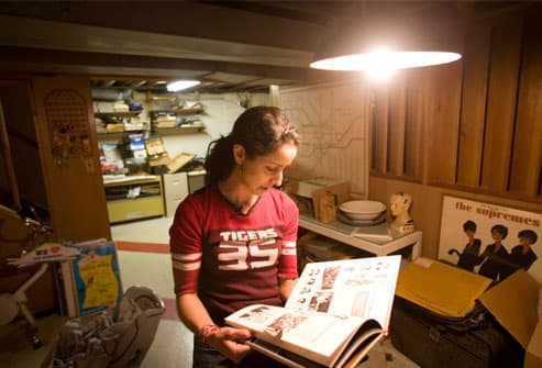 Woman looking at high school yearbook in basement