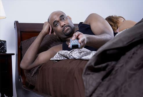 Mature couple in bed, man using remote control