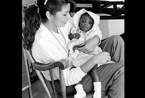 AIDS baby held by hospital worker in 1983