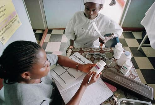 woman receives medicine in Nigerian AIDS clinic