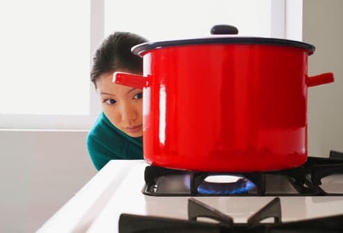 Woman checking stove burners