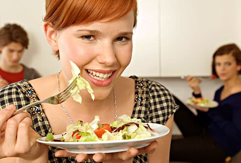 teen girl eating salad