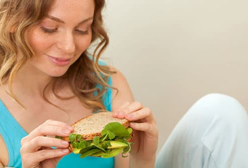 teen girl eating sandwich