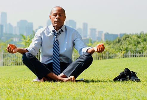 man meditating in park