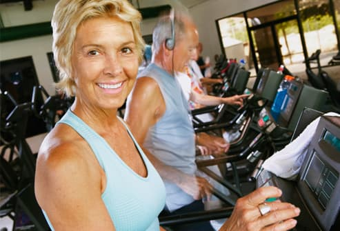 Senior woman using machine in gym