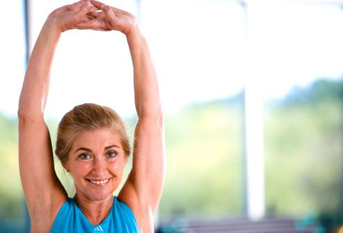 Trainer stretching her arms above her head