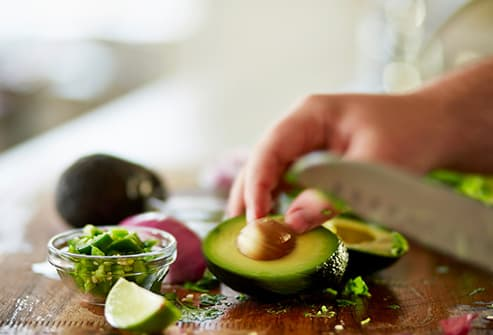person cutting an avocado
