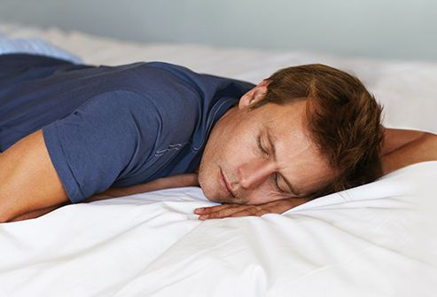 man sleeping on stomach in bed