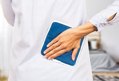 woman holding ice pack to lower back
