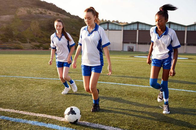 photo of teenage girls playing soccer