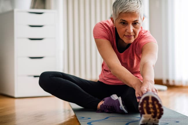 photo of woman stretching at home