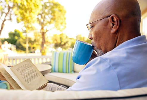 senior man reading book on patio