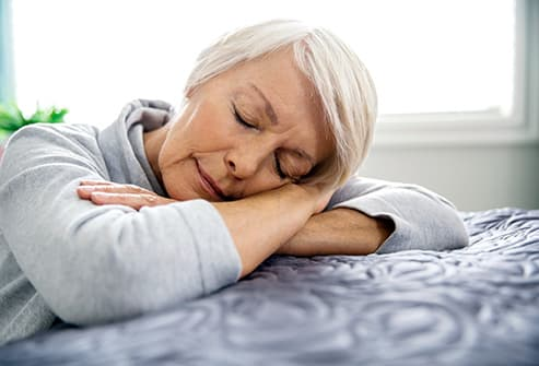 tired senior woman laying on edge of bed