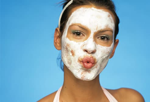 Young woman with face pack puckering lips