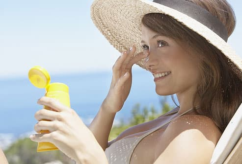 Teen wearing straw hat applying sunscreen