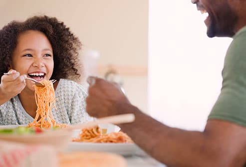 girl and dad eating pasta