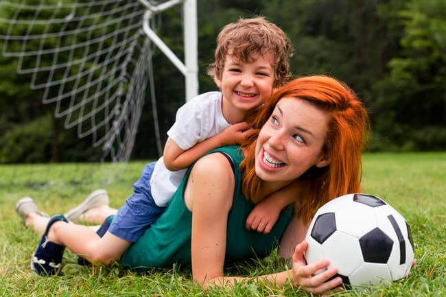 photo of mom playing soccer with son