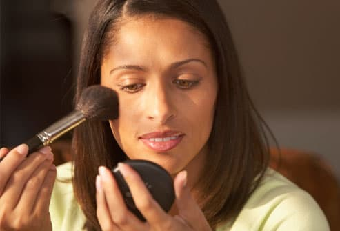 WOMAN APPLYING MAKE UP TO FACE