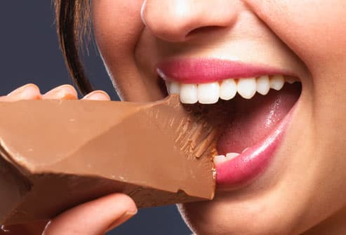 WOMAN BITING INTO CHOCOLATE BAR