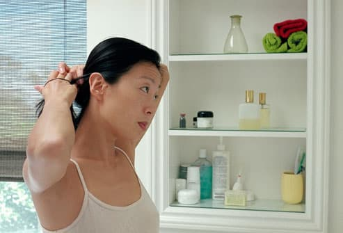 WOMAN IN BATHROOM FIXING HAIR