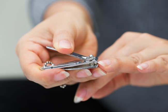photo of person clipping nails