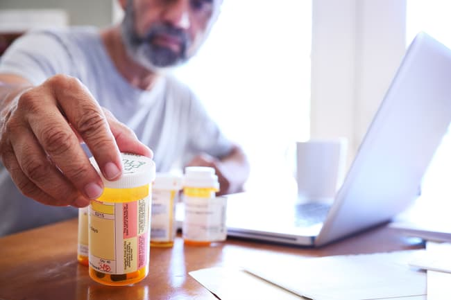photo of man reading medication bottles