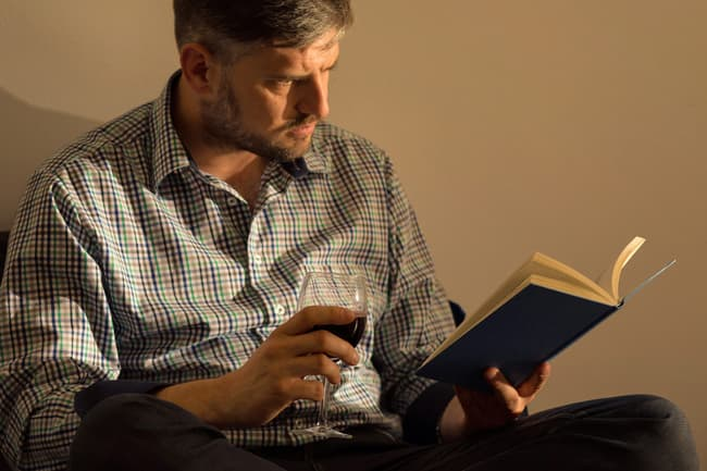 mature man reading book with glass of wine