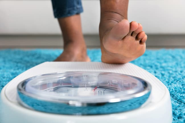 photo of foot stepping on scale