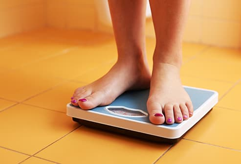 womans feet on weight scale