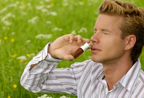 Man Using Nasal Spray in Field