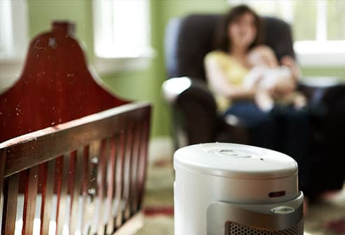 Electronic air cleaner in room near crib