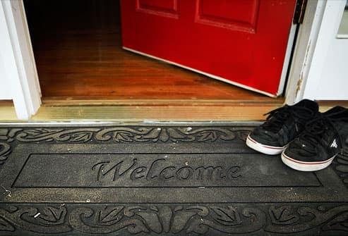 Shoes On Rubber Welcome Mat At Front Door