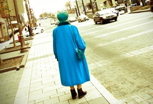 Elderly Woman Standing on Sidewalk