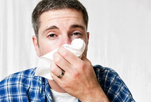 man with cold holding tissue to nose