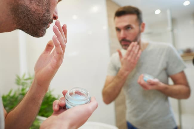 photo of man applying face cream