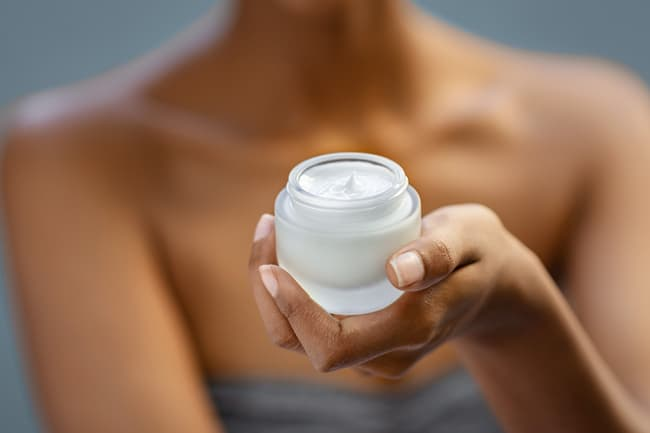 photo of woman holding jar of beauty moisturizer