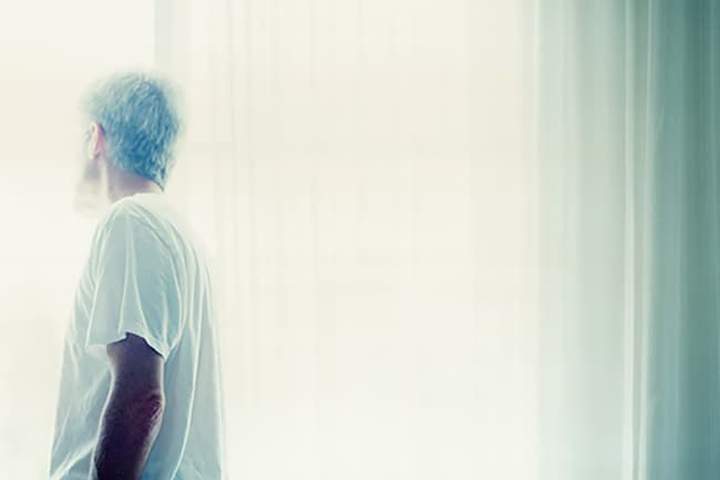 photo of man looking out window