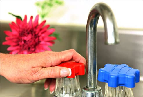 woman using sink knob grips