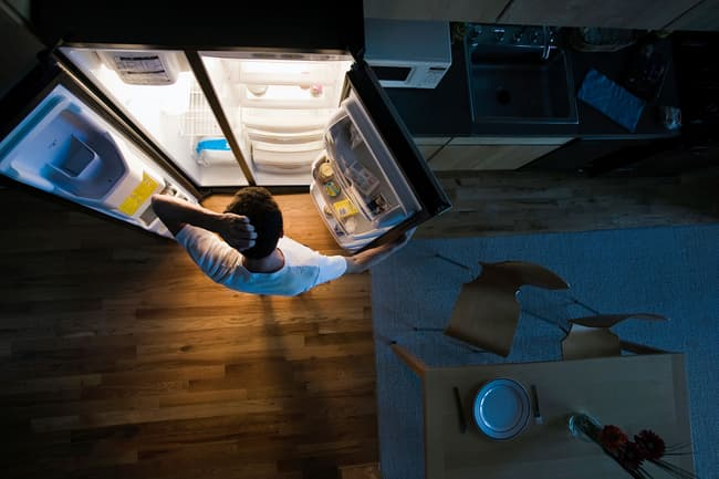 photo of man opening fridge