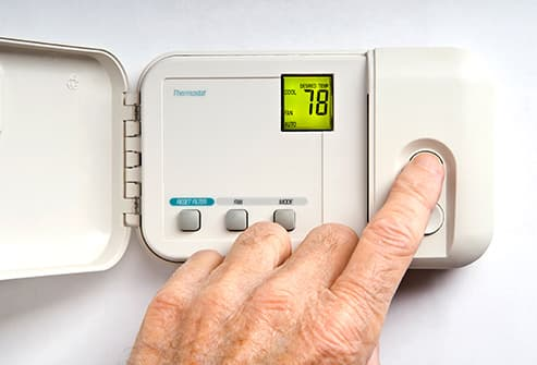 man adjusting thermostat close up