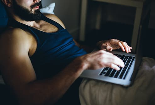 man working on laptop in bed