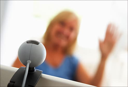 woman waving to webcam