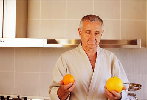 Puzzled man comparing an orange to a grapefruit