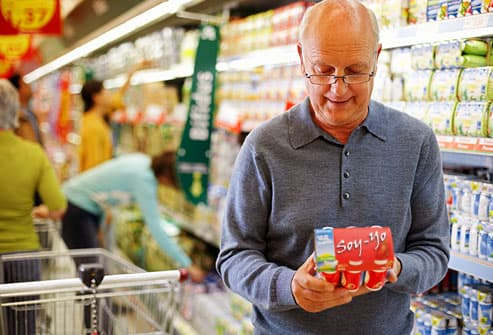 Senior man reading the label on soy yogurt carton