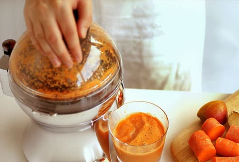 Woman making a carrot puree with food processor