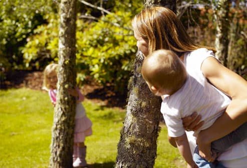Mother playing with daughters among birch trees