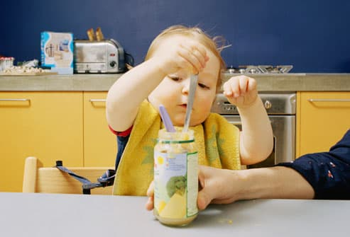 Baby eating with spoon from a jar