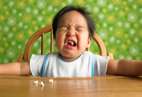 Toddler crying with popcorn in his mouth