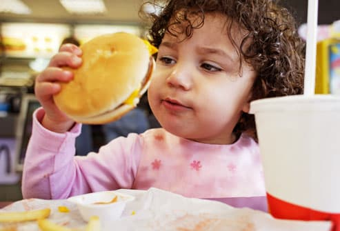 Toddler girl eating at a fast food chain