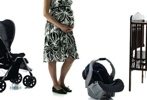 Pregnant woman beside stroller, car seat and crib